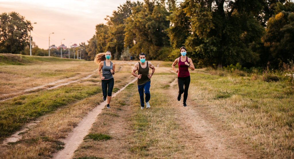 Three young active friends jogging together with protective face masks on.