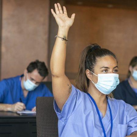 A female medical student attending a school lecture raises her hand to ask a question. The multi-ethnic group of adult students is wearing medical scrubs and protective face masks to prevent viral infection during the Covid-19 pandemic.