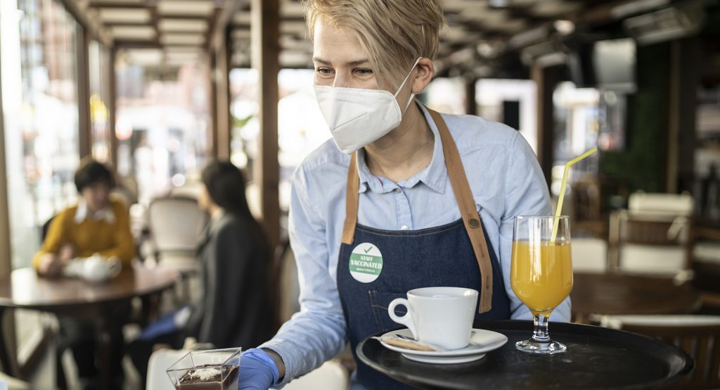 Young waitress wearing protective FFP2 mask and gloves serving to a customer. She is wearing a badge showing that she is vaccinated against COVID-19.